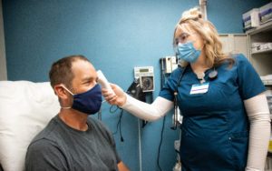 A nurse taking the temperature of a patient with a forehead infrared thermometer, both are wearing face masks.