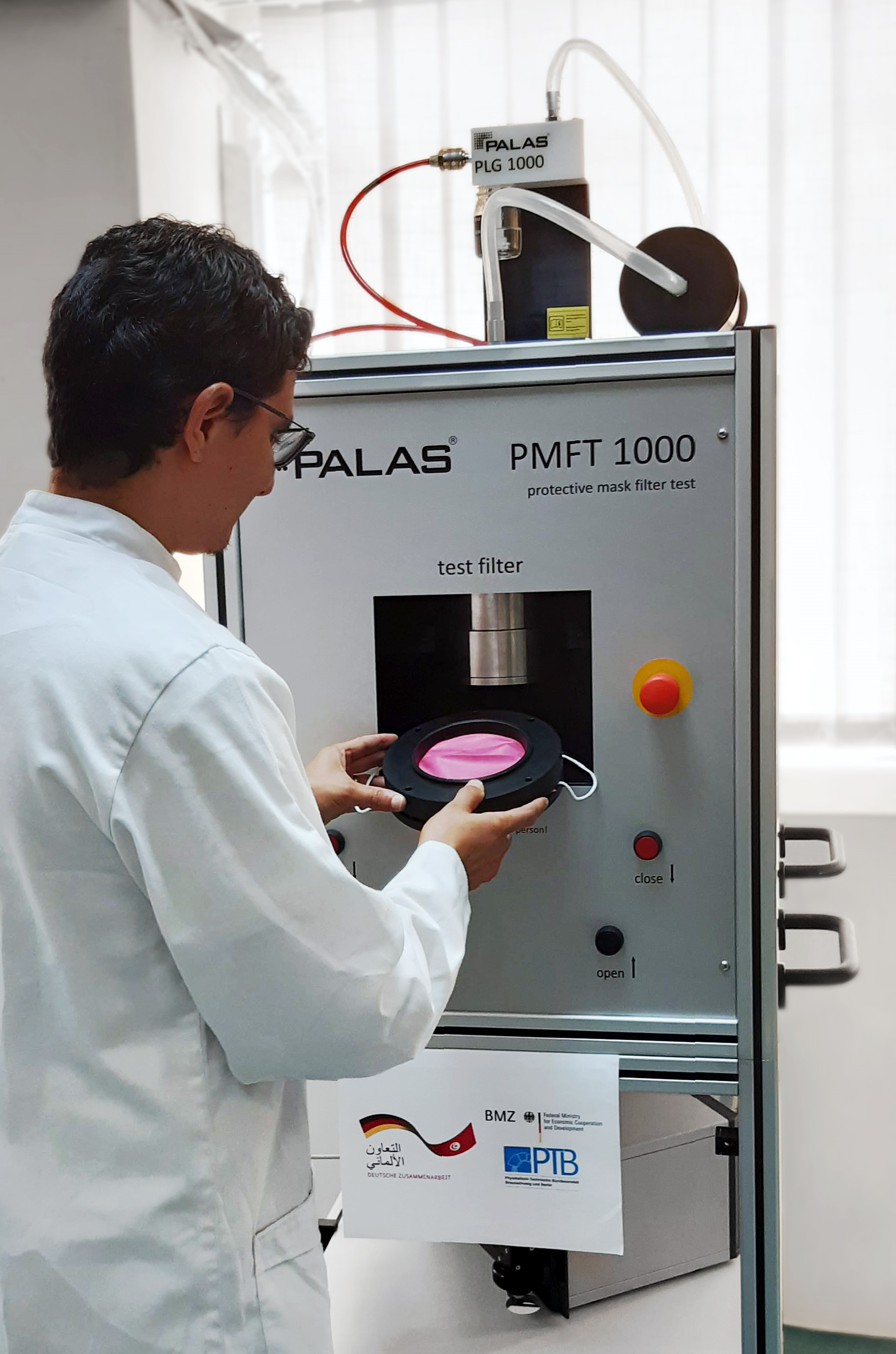 Laborkraft setzt rosafarbene Alltagsmaske in Prüfgerät ein.