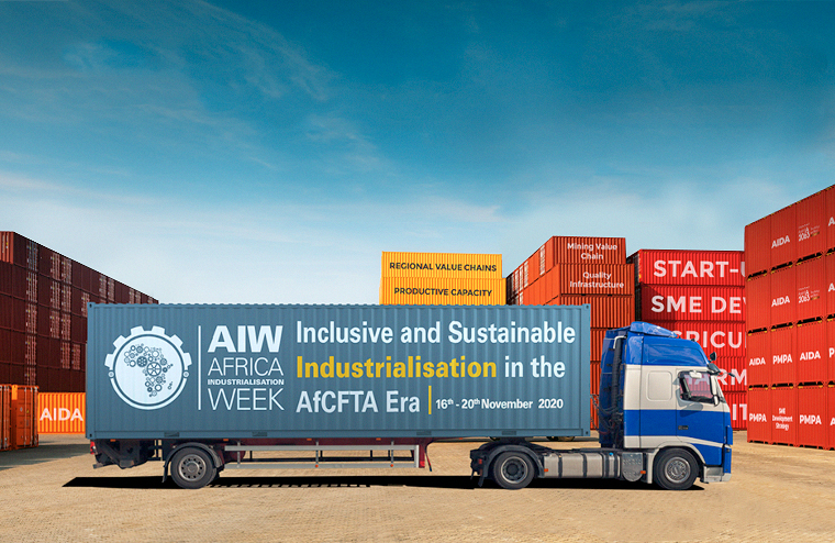 "A truck bearing the inscription ""Africa Industrialisation Week: Inclusive and Sustainable Industrialisation in the AfCFTA Era"" stands in front of red and orange containers."