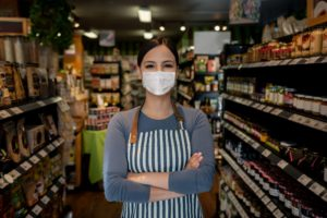 A business manager wearing a face mask while working the supermarket.