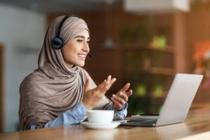 Young woman in hijab having video conference at cafe, using headset and laptop, drinking coffee, empty space