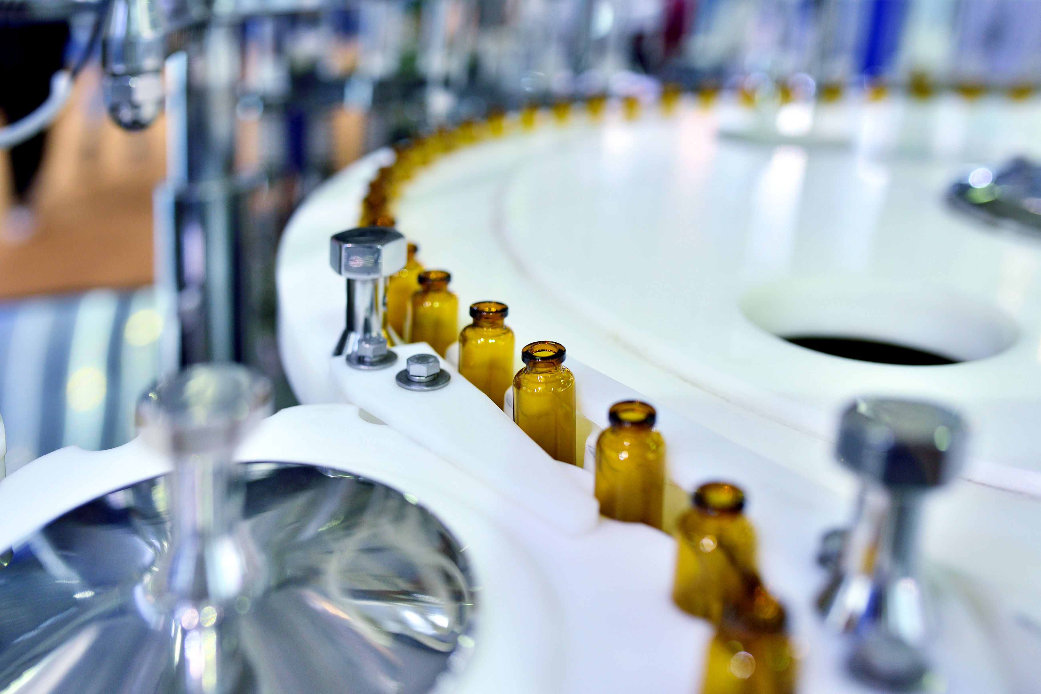 Close-up of brown glass bottles at turntable production line.